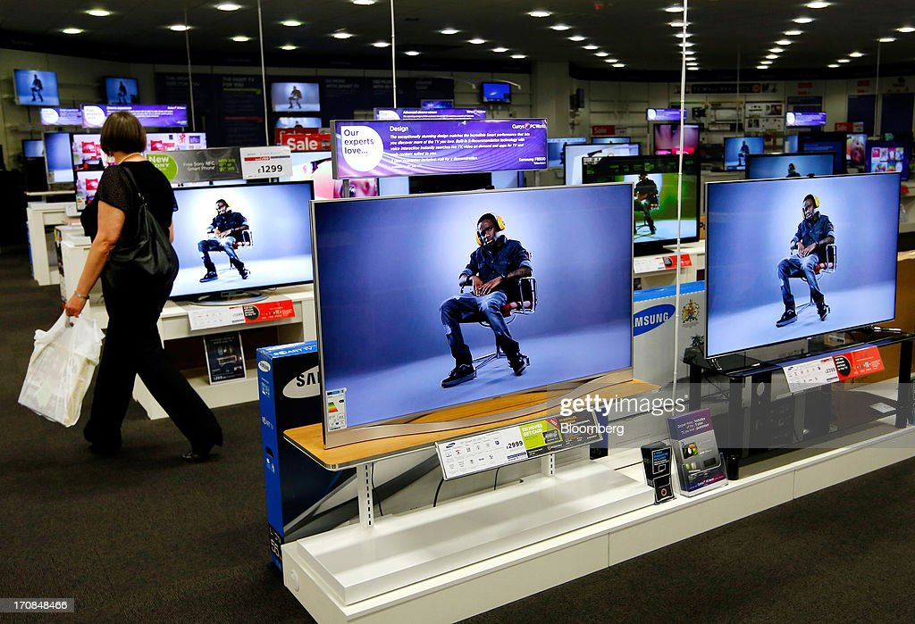 A customer browses a display of flat screen televisions inside a Currys and PC World 2 in 1 store, operated by Dixons Retail Plc, in Manchester, U.K., on Tuesday, June 18, 2013. Dixons Retail Plc, the U.K.'s largest consumer-electronics retailer, said last month it will report annual pretax profit at the 'top end' of analysts' predictions after fourth-quarter revenue beat estimates on increased sales of tablets and services such as software tutorials. Photographer: Paul Thomas/Bloomberg via Getty Images
