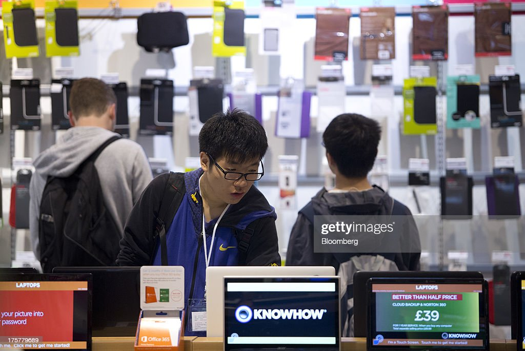 A customer browses a display of laptop computers inside a Currys and PC World 2 in 1 store, operated by Dixons Retail Plc, at the Westfield Stratford City retail complex in London, U.K., on Thursday, Aug. 8, 2013. U.K. consumer confidence rose to the highest in more than three years as Britons' optimism about the economic outlook improved. Photographer: Simon Dawson/Bloomberg via Getty Images