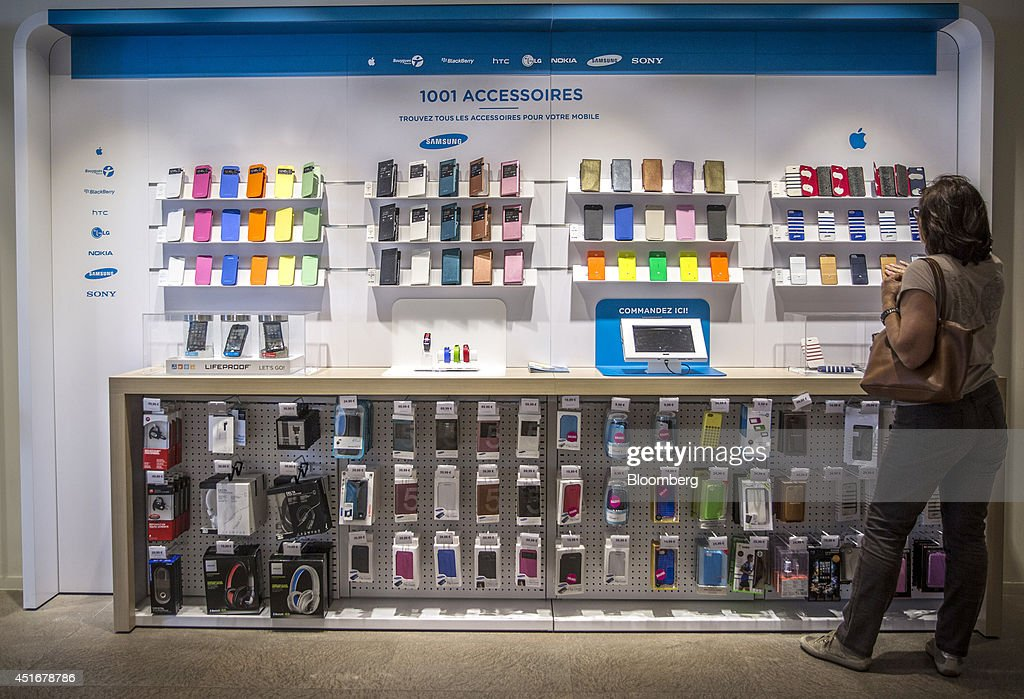 A customer browses a row of protective cases for the Apple Inc. iPhone 5s series as they sit on display inside a Bouygues Telecom store, operated by Bouygues SA in Paris, France, on Thursday, July 3, 2014. Bouygues Telecom, France's third-largest mobile operator, was looking for a buyer as profitability and cash generation declined. Photographer: Balint Porneczi/Bloomberg via Getty Images