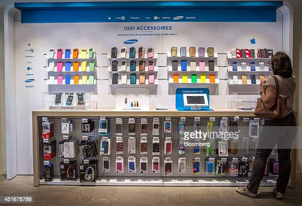 A customer browses a row of protective cases for the Apple Inc iPhone 5s series as they sit on display inside a Bouygues Telecom store operated by...