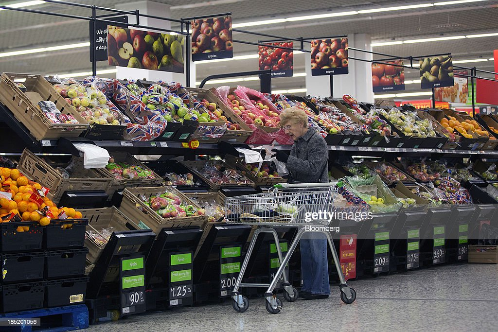 A customer browses apples on the fresh fruit and vegetable aisle inside an Asda supermarket, the U.K. retail arm of Wal-Mart Stores Inc., in Watford, U.K., on Thursday, Oct. 17, 2013. U.K. retail sales rose more than economists forecast in September as an increase in furniture demand led a rebound from a slump the previous month. Photographer: Simon Dawson/Bloomberg via Getty Images