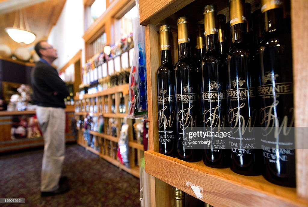 A customer browses as bottles of Vidal Blanc ice wine are displayed for sale at the Ferrante Winery in Geneva, Ohio, U.S., on Friday, Jan. 4, 2013. Ice wine is a type of dessert wine produced from grapes that have been frozen while still on the vine, because the sugars and other dissolved solids do not freeze, but the water does, this allows a more concentrated grape must to be pressed. Photographer: Ty Wright/Bloomberg via Getty Images