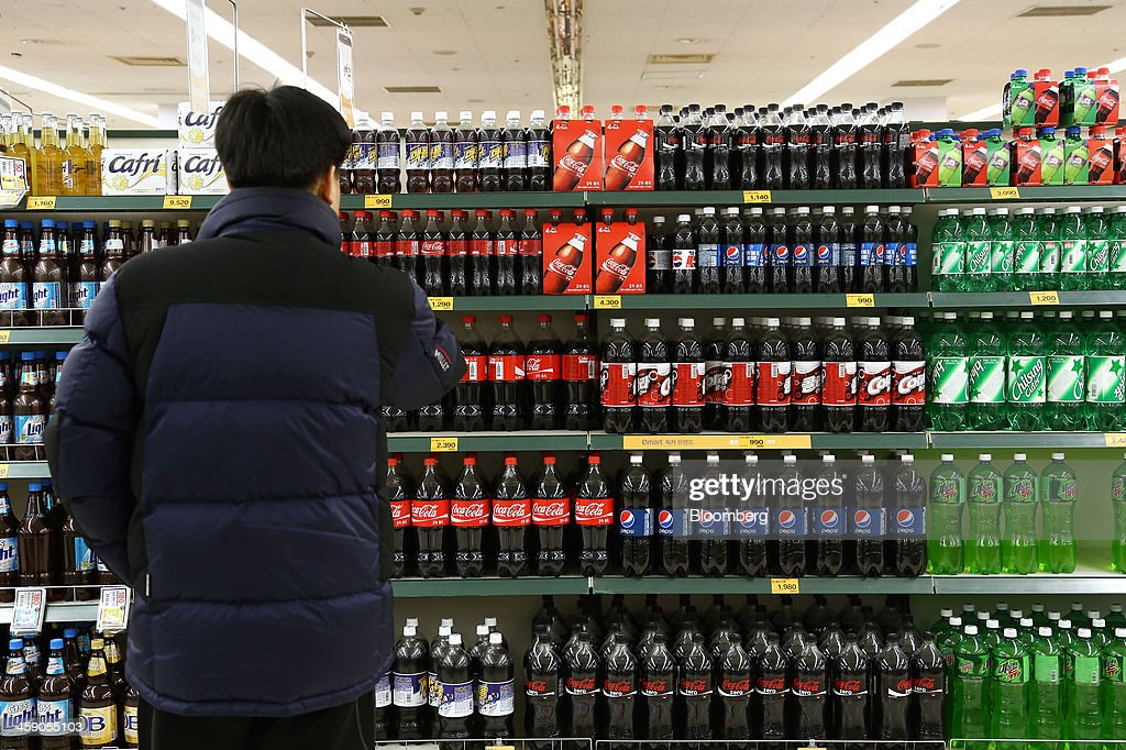 A customer browses bottles of beer and soda at an E-Mart Co. store, a subsidiary of Shinsegae Co., in Incheon, South Korea, on Saturday, Dec. 21, 2013. Consumer prices climbed 0.9 percent in November from a year earlier after a 0.7 percent increase in October that was the smallest gain since July 1999. Photographer: SeongJoon Cho/Bloomberg via Getty Images