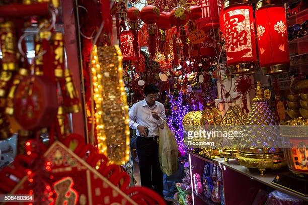 A customer browses decorations on sale for Lunar New Year at a market stall in the Sham Shui Po district of Hong Kong China on Thursday Feb 4 2016...
