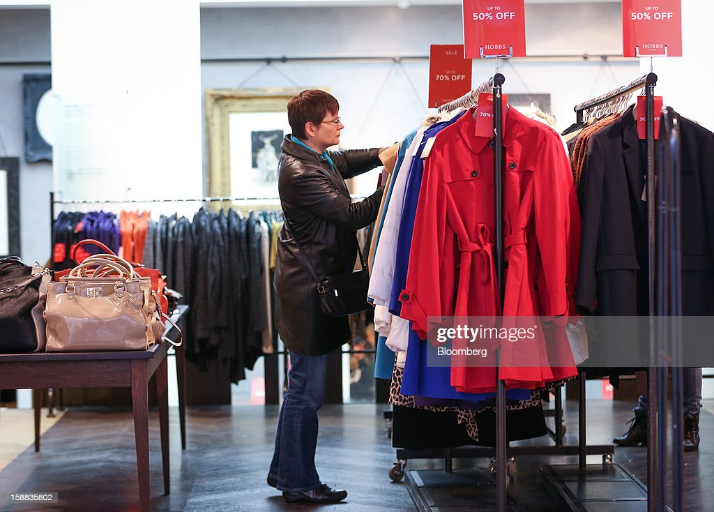 A customer browses discounted clothing hanging from a rail in a Hobbs fashion store in the Covent Garden district of London, U.K., on Monday, Dec. 31, 2012. The number of Britons making shopping trips for post-holiday bargains barely increased on the day after Christmas as more people sought discounts online. Photographer: Jason Alden/Bloomberg via Getty Images