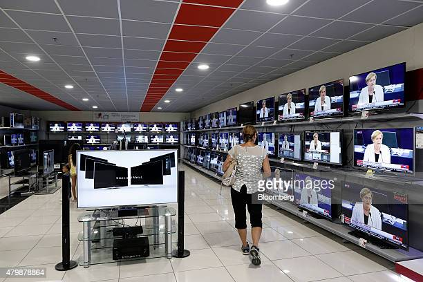 A customer browses flat screen televisions inside an Electroniki household appliance store operated by Electroniki Athinon SA in Thessaloniki Greece...