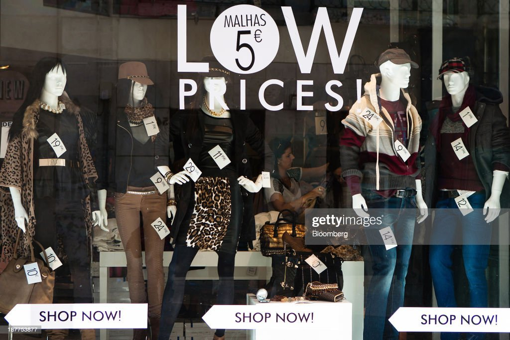 A customer browses goods for sale inside a fashion store advertising low prices in its window in Lisbon, Portugal, on Tuesday, Nov. 12, 2013. Portugal's jobless rate dropped for a second quarter, falling to 15.6 percent in the three months through September as the country's economy shows signs of recovery. Mario Proenca/Bloomberg via Getty Images