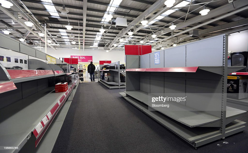 A customer browses goods near empty shelving units inside a Comet electronics store in Slough, U.K., on Friday, Nov. 23, 2012. Comet, a U.K. electronics chain, appointed Deloitte LLP as insolvency administrator, less than a year after being bought by private-equity firm OpCapita LLP. Photographer: Chris Ratcliffe/Bloomberg via Getty Images