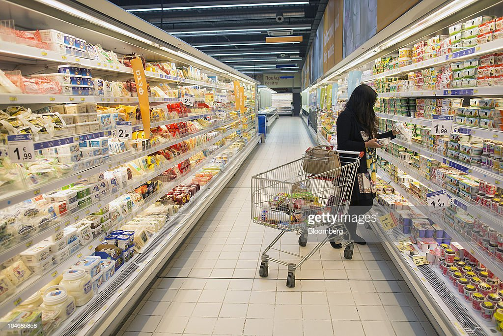 A customer browses goods on display in the dairy aisle of a Carrefour SA supermarket at the Mall of Cyprus in Nicosia, Cyprus, on Tuesday, March 26, 2013. Controls on capital movements to prevent money from draining out of the banking system -- allowed in exceptional circumstances under European Union law -- will remain for 'a matter of weeks,' Cypriot Finance Minister Michael Sarris said. Photographer: Simon Dawson/Bloomberg via Getty Images