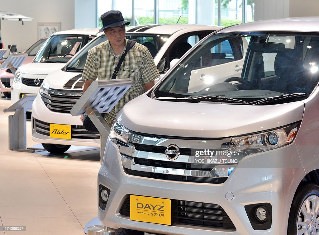A customer browses Japanese auto giant Nissan Motor's mini car Days at the company's showroom in Yokohama, suburban Tokyo on July 25, 2013. Nissan on July 25 said its April-June net profit jumped 14 percent to $821 million, as it pointed to improved market share in Japan and North America. AFP PHOTO / Yoshikazu TSUNO