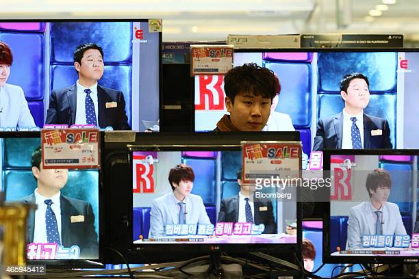 A customer browses LG Electronics Inc and Samsung Electronics Co televisions at a Hyundai I'Park Mall department store majorityowned by Hyundai...