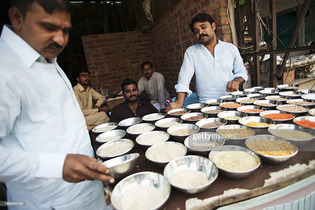 A customer browses rice samples at a market in the district of Faisalabad in Punjab, Pakistan, on Sunday, Oct. 13, 2013. Prime Minister Nawaz Sharifs four-month-old government is struggling to revive the $231 billion economy crippled by chronic energy shortages and a spike in violence from a Taliban insurgency in the northwest. Photographer: Asad Zaidi/Bloomberg via Getty Images