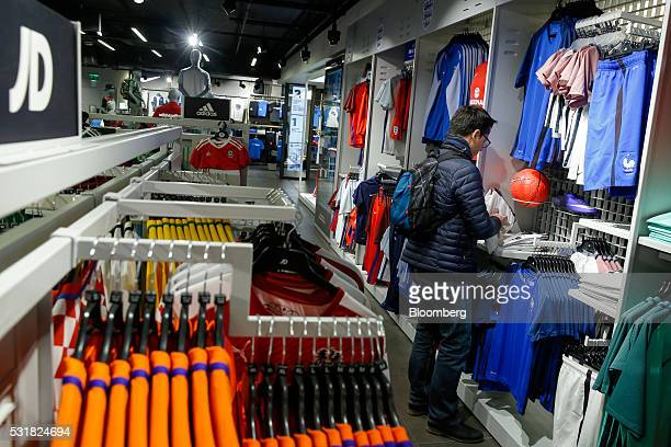 A customer browses soccer kits at a JD Sports Fashion Plc sportswear retail store on Oxford Street in London UK on Thursday April 28 2016 With a...