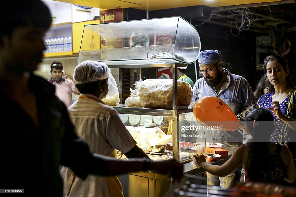 A customer browses the snacks at a panipuri stall at a food court in the suburb of Bandra in Mumbai, India, on Saturday, July 6, 2013. India's consumer price index (CPI) figures for June are scheduled to be released on July 12. Photographer: Dhiraj Singh/Bloomberg via Getty Images