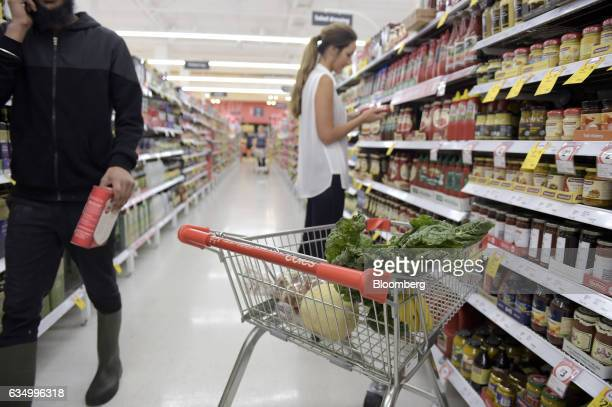 A customer browses through grocery items as a shopping cart stands nearby at a Coles supermarket operated by Wesfarmers Ltd in the Richmond area of...