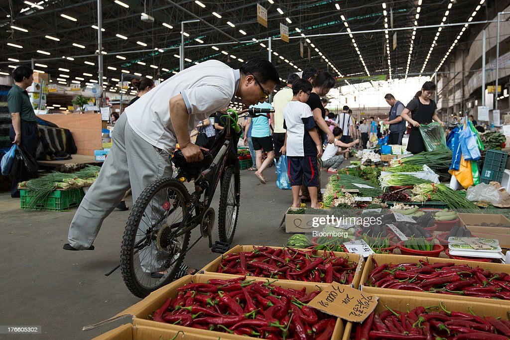 A customer browses vegetables at Samsan Agricultural Wholesale Market in Incheon, South Korea, on Friday, Aug. 16, 2013. South Korean producer prices declined 0.9 percent in July from a year earlier after a 1.4 percent drop in June, the central bank said in a statement today. Photographer: SeongJoon Cho/Bloomberg via Getty Images