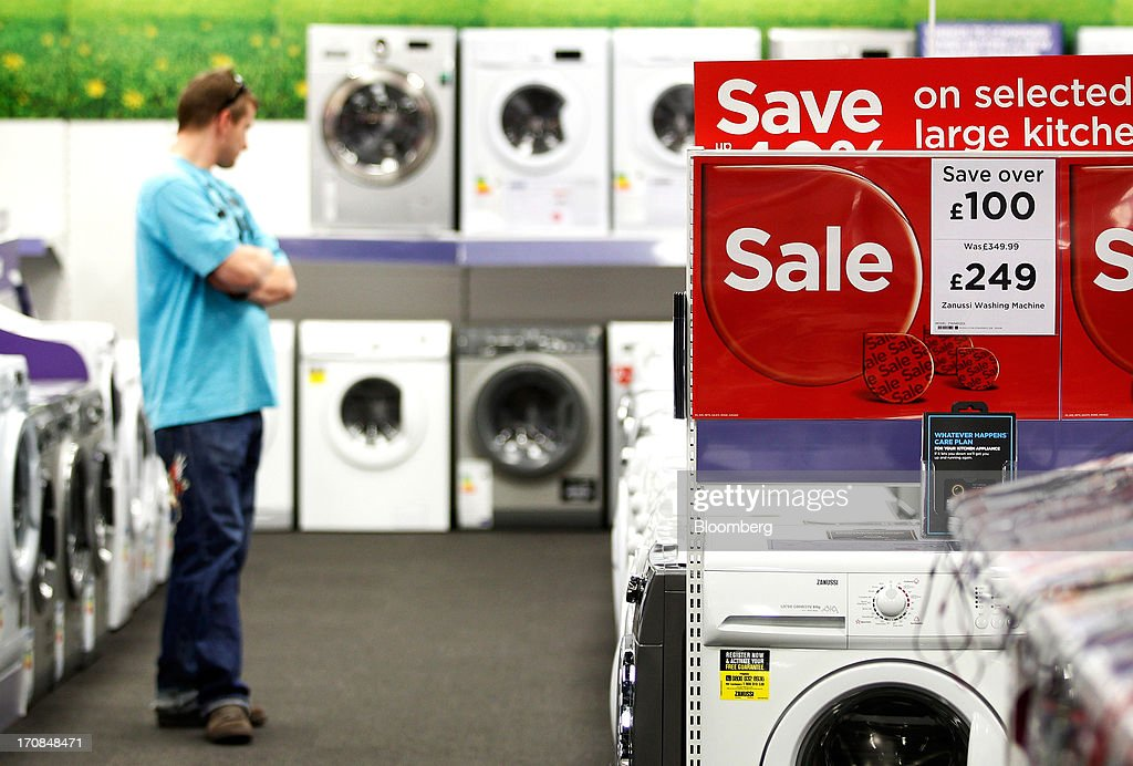 A customer browses washing machines displayed for sale inside a Currys and PC World 2 in 1 store, operated by Dixons Retail Plc, in Manchester, U.K., on Tuesday, June 18, 2013. Dixons Retail Plc, the U.K.'s largest consumer-electronics retailer, said last month it will report annual pretax profit at the 'top end' of analysts' predictions after fourth-quarter revenue beat estimates on increased sales of tablets and services such as software tutorials. Photographer: Paul Thomas/Bloomberg via Getty Images