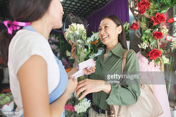 Customer Buying Bunch Of Flowers In Flower Shop