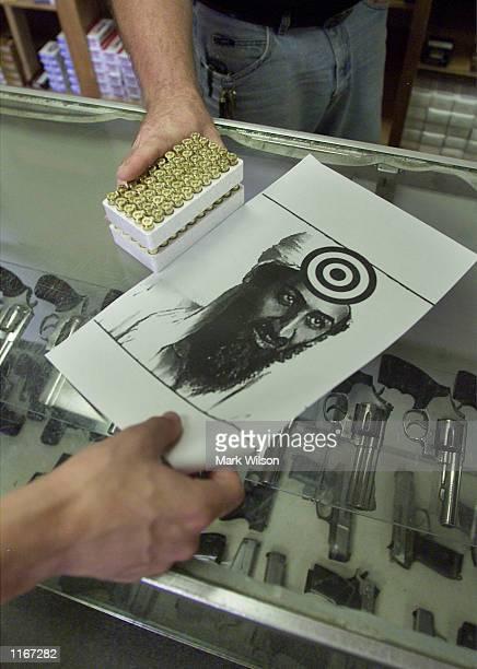 A customer buys a box of bullits and a target of Osama Bin Laden October 3 2001 at Blue Ridge Arsenal in Chantilly VA Guns sales have risen across...