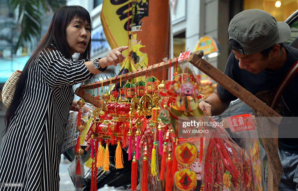 A customer buys a Chinese decoration from a sidewalk vendor selling goods for the Chinese Lunar New Year in the Indonesian capital city of Jakarta on February 9, 2013 the country's minority Chinese-Indonesians prepare to celebrate the Chinese New Year. The Year of the Snake falls across the region on February 10. AFP PHOTO / Bay ISMOYO