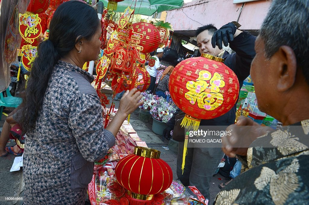 A customer buys a Chinese lantern from a sidewalk vendor selling goods for Chinese Lunar New Year in the Indonesian capital city of Jakarta on February 8, 2013 as the Muslim majority country's minority Chinese-Indonesians prepares to celebrate the Chinese Lunar New Year. The 'Year of the Snake' falls across the region on February 10, 2013.