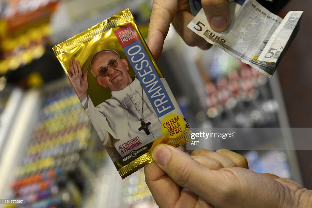 A customer buys a pack of the new stickers dedicated to Pope Francis to collect in an album of 400 images on sale in a tobacco and newspapers seller on March 28, 2013 in Rome. A pack of five stickers costs 0,60 euro. AFP PHOTO / ANDREAS SOLARO