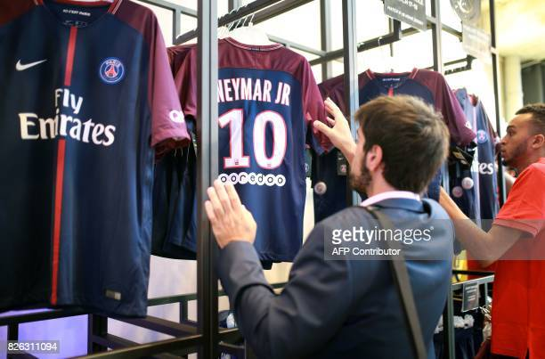 A customer buys a ParisSaintGermain Neymar's number 10 jersey at the ParisSaintGermain football club store on the Champs Elysees avenue in Paris on...