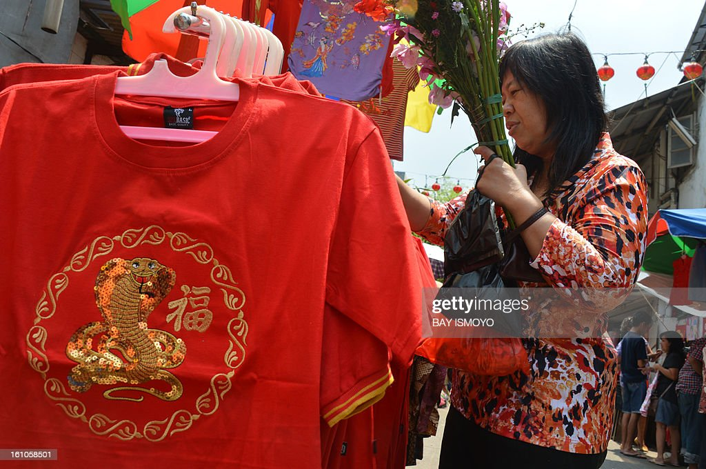 A customer buys a t-shirt with snake design from a sidewalk vendor selling goods for the Chinese Lunar New Year in the Indonesian capital city of Jakarta on February 9, 2013 the country's minority Chinese-Indonesians prepare to celebrate the Chinese New Year. The Year of the Snake falls across the region on February 10. AFP PHOTO / Bay ISMOYO