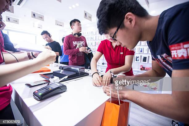A customer buys a Xiaomi phones during the first day of the high configuration Xiaomi Note to be on sale at a Xiaomi experience store on May 12 2105...