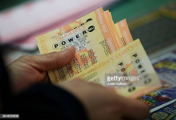 A customer buys Powerball tickets at Kavanagh Liquors on January 13 2016 in San Lorenzo California Dozens of people lined up outside of Kavanagh...
