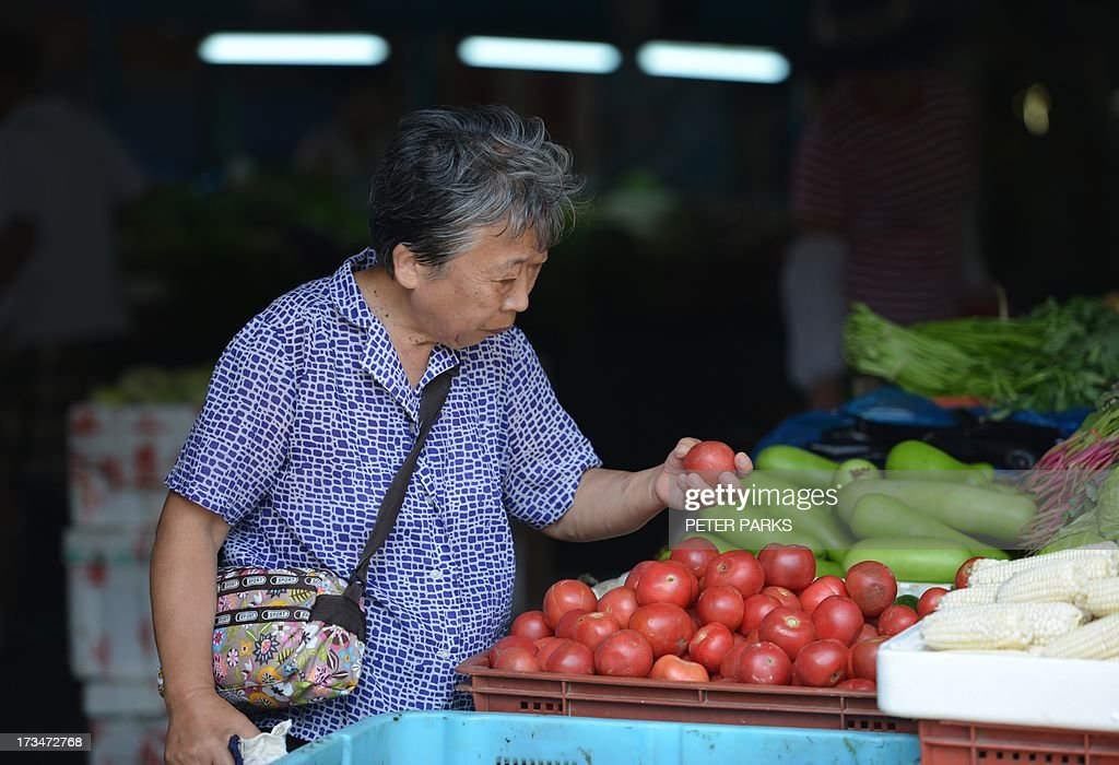 A customer buys tomatoes in a market in Shanghai on July 15, 2013. China's gross domestic product expanded 7.5 percent in the April-June quarter, official data showed, a second consecutive slowdown in growth as worries mount over the health of the world's number two economy. AFP PHOTO/Peter PARKS