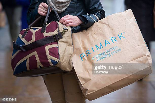 A customer carriers her shopping purchases inside a Primarkbranded paper bag after leaving a Primark clothing store operated by Associated British...