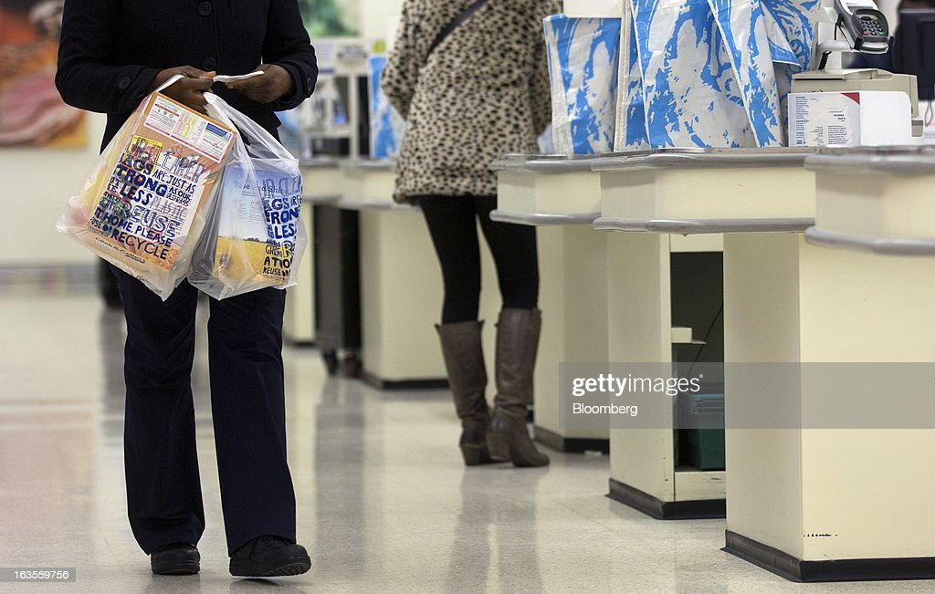 A customer carriers produce in plastic shopping bags after paying for her goods inside a Tesco Plc supermarket in the borough of Kensington in London, U.K., on Tuesday, March 12, 2013. Tesco Plc, the U.K.'s largest grocer launched a 'Price Promise', its latest initiative offering to match the price of customers' purchases to that of it's rivals, including Wal-Mart Stores Inc.'s ASDA. Photographer: Simon Dawson/Bloomberg via Getty Images
