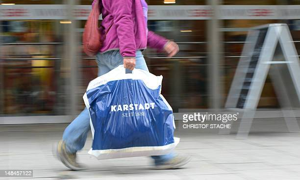 A customer carries a bag with the logo of German retail chain Karstadt in front of a Karstadt department store in Munich southern Germany on July 17...