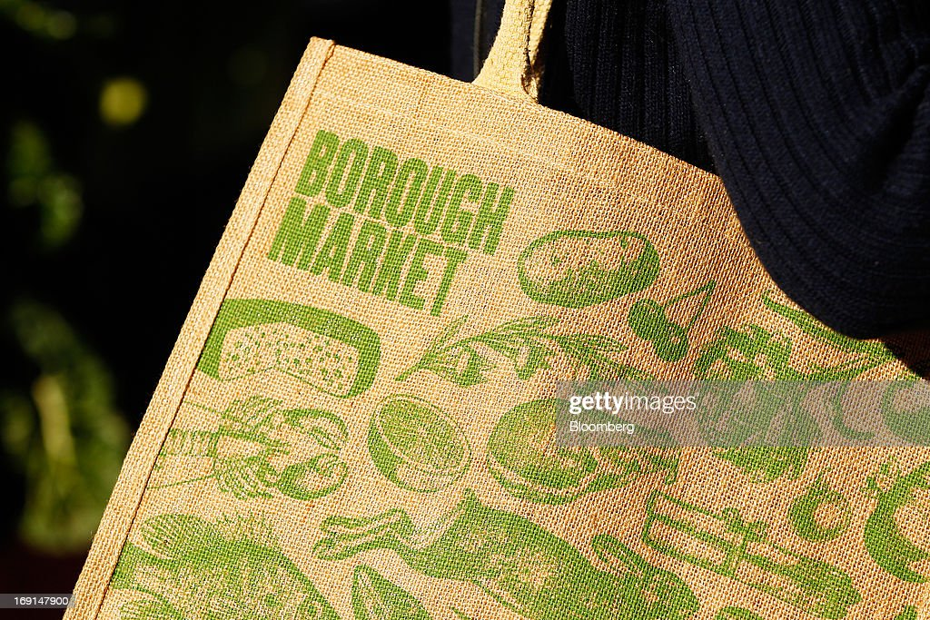 A customer carries a Borough Market-branded shopping bag at the Frenchs Forest Organic Food Market in Sydney, Australia, on Sunday, May 19, 2013. The Reserve Bank of Australia cut its benchmark interest rate to a record low this month to boost businesses weakened by the currency's sustained strength, even as households reacted to earlier reductions. Photographer: Brendon Thorne/Bloomberg via Getty Images