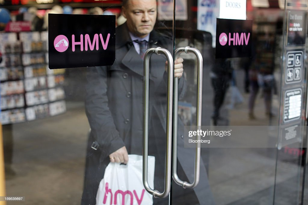 A customer carries a branded shopping bag as he exits an HMV store in London, U.K., on Tuesday, Jan. 15, 2013. Endless LLP, a private-equity firm that focuses on companies in distress, contacted HMV Group Plc's prospective administrators with a view to buying the U.K.'s biggest retailer of CDs and DVDs. Photographer: Simon Dawson/Bloomberg via Getty Images