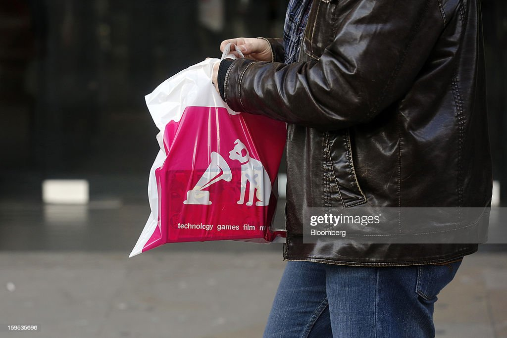 A customer carries a branded shopping bag as he leaves an HMV store in London, U.K., on Tuesday, Jan. 15, 2013. Endless LLP, a private-equity firm that focuses on companies in distress, contacted HMV Group Plc's prospective administrators with a view to buying the U.K.'s biggest retailer of CDs and DVDs. Photographer: Simon Dawson/Bloomberg via Getty Images