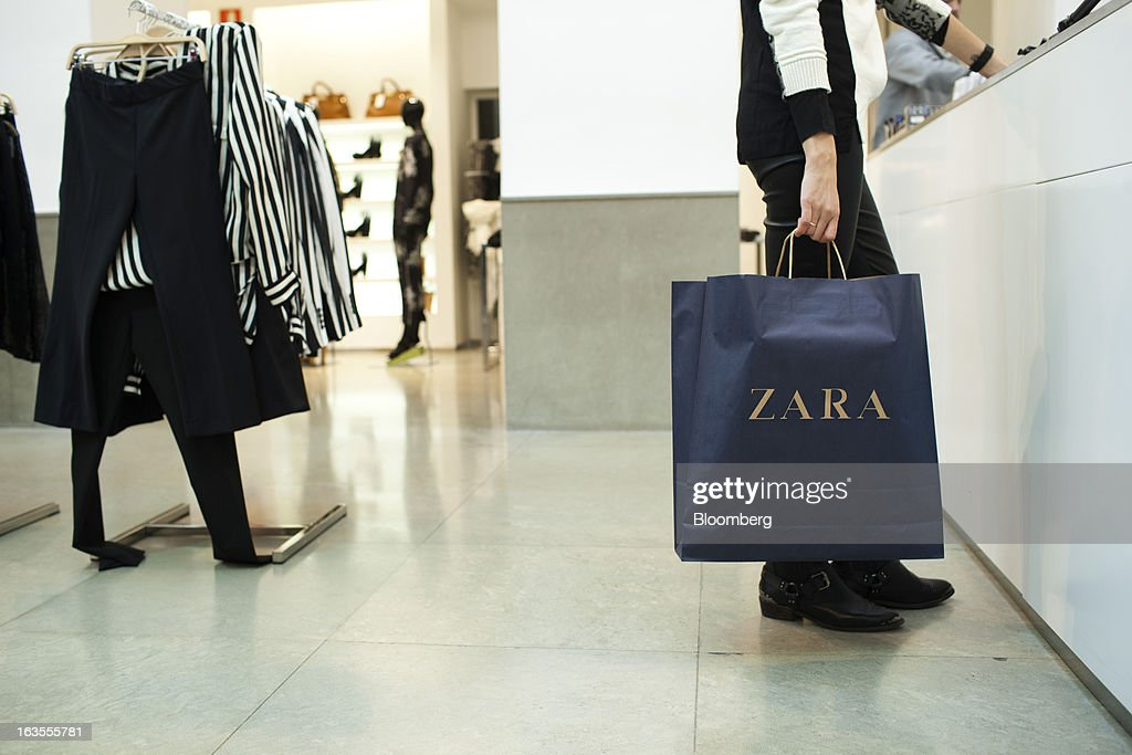 A customer carries a branded shopping bag at the service desk of a Zara fashion store, operated by Inditex SA, in Madrid, Spain, on Tuesday, March 12, 2013. Europe's richest man, Amancio Ortega, the 76-year-old founder of Inditex SA, the world's biggest clothing retailer and owner of the Zara clothing chain, is No. 3 on Standard & Poor's 500 Index with a net worth of $57.4 billion, $4.9 billion ahead of Warren Buffett, 82. Photographer: Angel Navarrete/Bloomberg via Getty Images