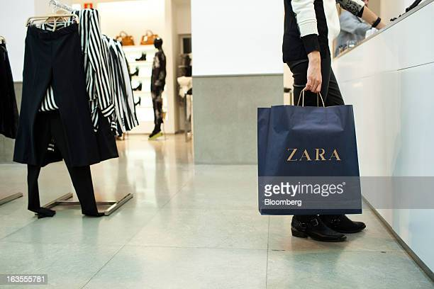 A customer carries a branded shopping bag at the service desk of a Zara fashion store operated by Inditex SA in Madrid Spain on Tuesday March 12 2013...
