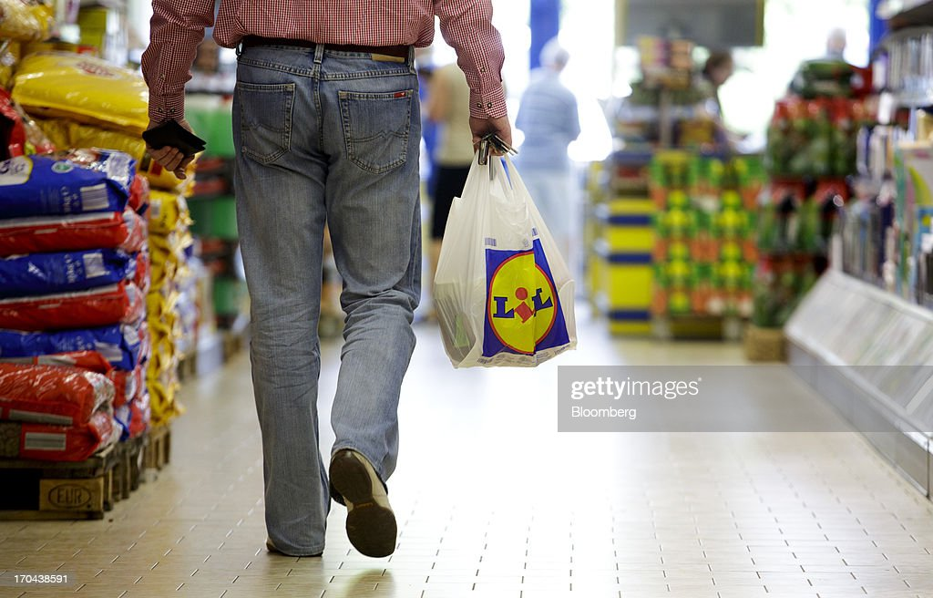 A customer carries a branded shopping bag inside a Lidl discount supermarket store, operated by Schwarz Group, in Prague, Czech Republic, on Thursday, June 13, 2013. Ahold and Tesco are tied as the Czech Republic's third-largest grocer by revenue behind Lidl discount store owner Schwarz Group and Rewe AV, which owns the Billa supermarkets, according to Krakow, Poland-based market researcher PMR. Photographer: Martin Divisek/Bloomberg via Getty Images