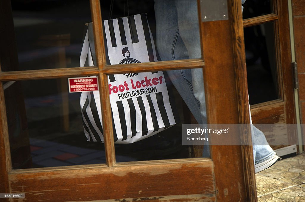 A customer carries a Foot Locker Inc. shopping bag in San Francisco, California, U.S., on Tuesday, March 5, 2013. Foot Locker Inc. is expected to release earnings data on March 8. Photographer: David Paul Morris/Bloomberg via Getty Images