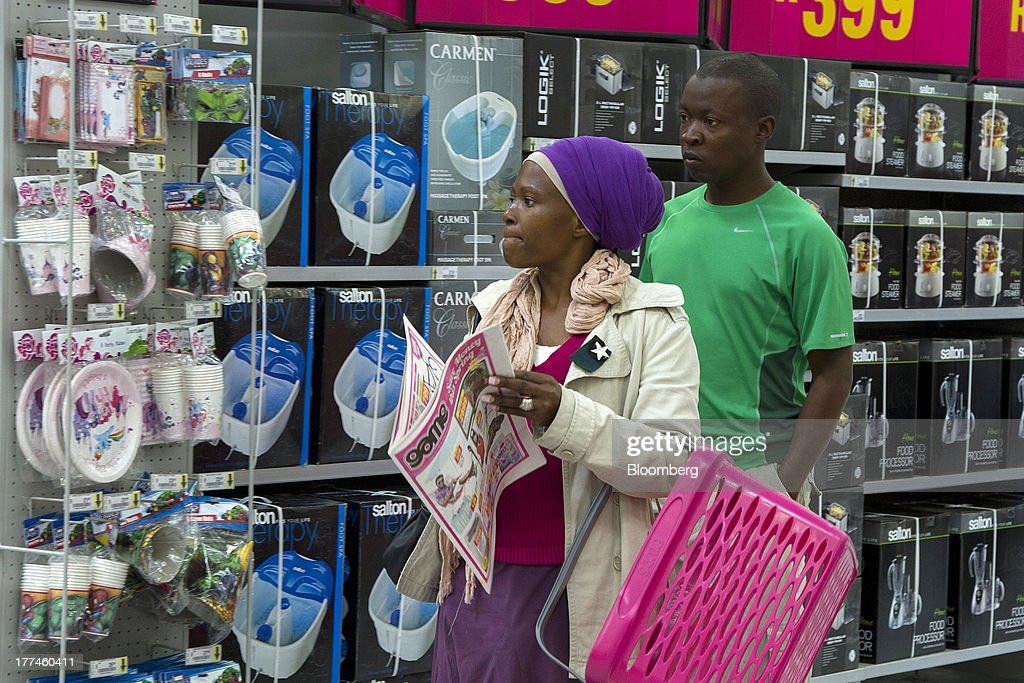 A customer carries a newspaper advertising special offers as she browses electronic goods for sale inside a Game supermarket, part of Massmart Holdings Ltd., in the Fourways district of Johannesburg, South Africa, on Thursday, Aug. 22, 2013. Massmart Holdings Ltd., the South African food and goods wholesaler owned by Wal-Mart Stores Inc., said revenue growth continued to slow in August after a downturn in consumer spending hurt first-half earnings. Photographer: Nadine Hutton/Bloomberg via Getty Images