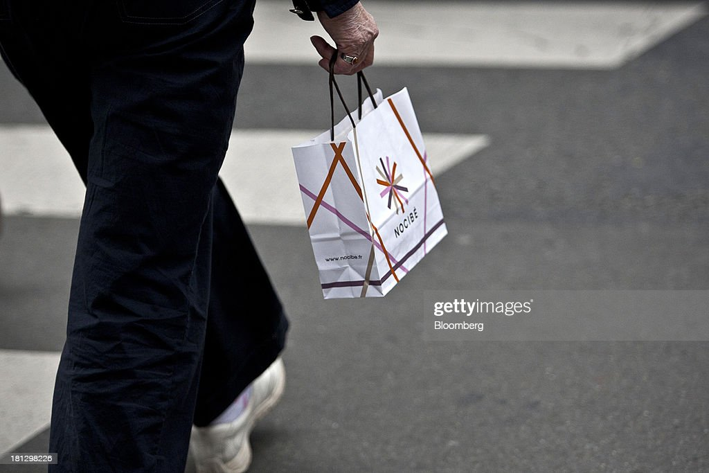 A customer carries a Nocibe SA paper bag after shopping at the company's beauty store in Paris, France, on Thursday, Sept. 19, 2013. Bank of France General Council member Bernard Maris said France will end up restructuring its debt as tax 'optimization' by large companies including Google Inc. will leave too big a burden on the middle class. Photographer: Balint Porneczi/Bloomberg via Getty Images
