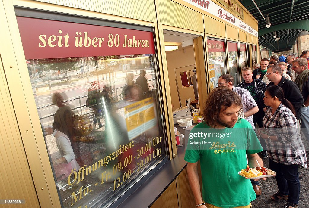 A customer carries a plate of currywurst with french fries at Konnopke's currywurst stand on July 14, 2012 in Berlin, Germany. Currywurst, originally founded in post-war Berlin by Herta Heuwa, is Berlin's answer to fast food and is sold at specialized stands across the city and the rest of Germany. Currywurst is pork sausage, with or without casing, fried or deep-fried, that is typically smothered in curry powder and a ketchup-like sauce called curry sauce and served with french fries.