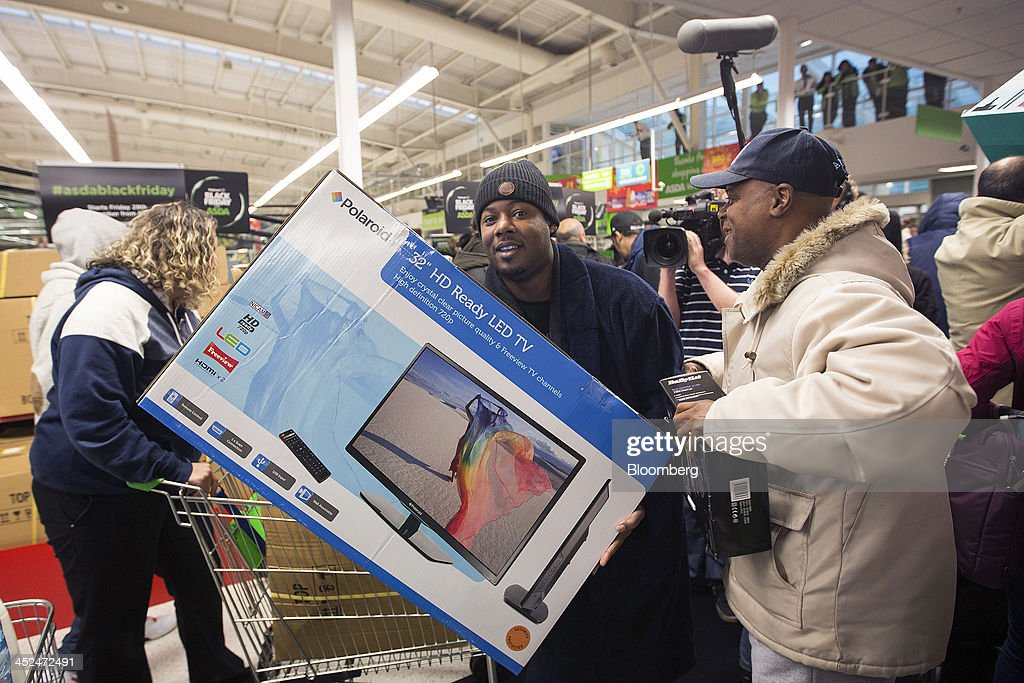 A customer carries a Polaroid Corp. LED television during a Black Friday discount sale inside an Asda supermarket in Wembley, London, U.K., on Friday, Nov. 29, 2013. Britons queued outside Asda supermarkets this morning and charged into stores when doors opened at 8 a.m. as the U.K. grocery chain took on the Black Friday mantle from U.S. owner Wal-Mart Stores Inc. Photographer: Simon Dawson/Bloomberg via Getty Images