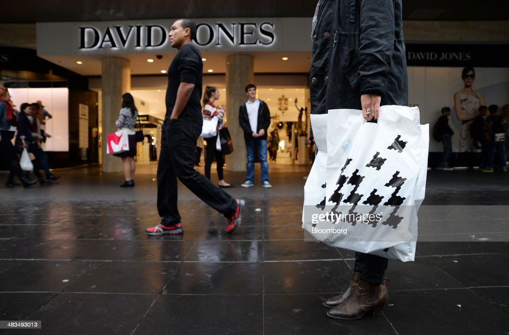 A customer carries a shopping bag featuring the houndstooth branding of David Jones Ltd outside the company's Bourke Street store in Melbourne...