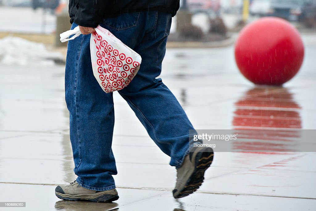 A customer carries a shopping bag outside a Target Corp. store in Peru, Illinois, U.S., on Thursday, Feb. 7, 2013. Target Corp. led U.S. retailers to the biggest monthly same-store sales gain in more than a year as shoppers snapped up discounted merchandise chains were clearing out after the holidays. Photographer: Daniel Acker/Bloomberg via Getty Images