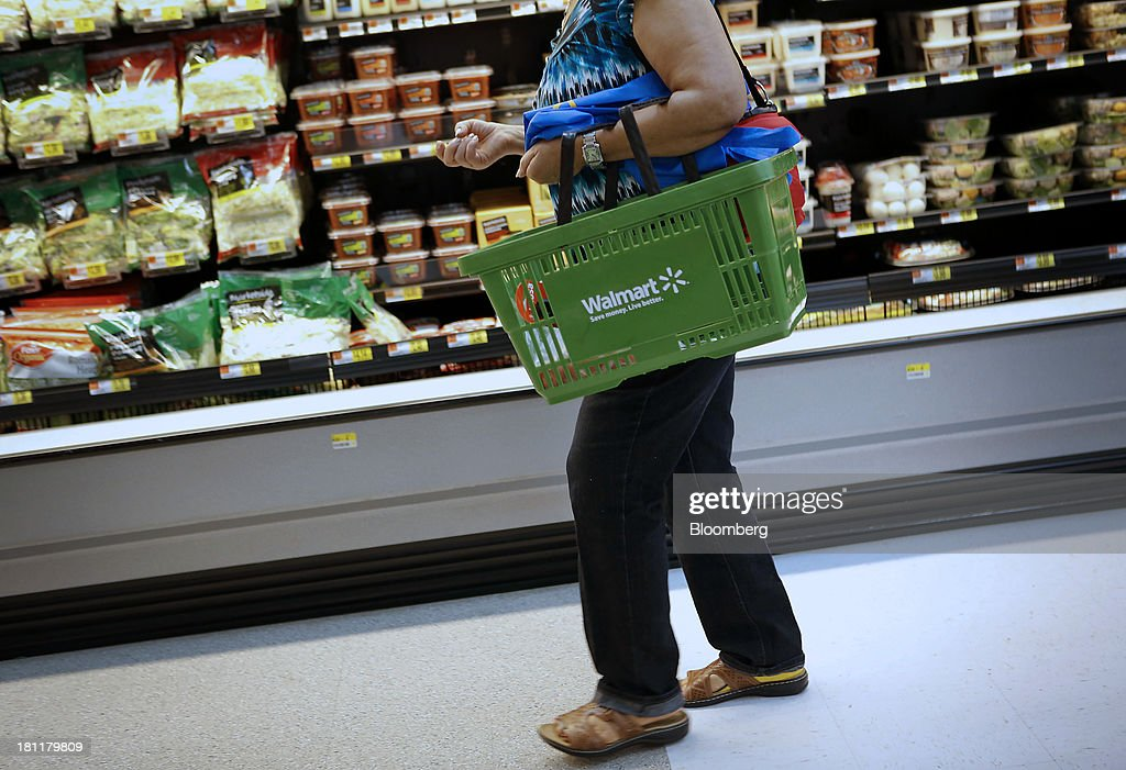 A customer carries a shopping basket during the grand opening of a Wal-Mart Stores Inc. location in the Chinatown neighborhood of Los Angeles, California, U.S., on Thursday, Sept. 19, 2013. Wal-Mart Stores Inc. will phase out 10 chemicals it sells in favor of safer alternatives and disclose the chemicals contained in four product categories, the company announced Sept. 12. Photographer: Patrick T. Fallon/Bloomberg via Getty Images