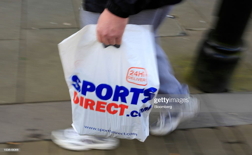 A customer carries a Sports Direct International Plc branded shopping bag in Oldham, U.K., on Saturday, Oct. 6, 2012. JJB Sports Plc, a U.K. sporting goods retailer, will close most of its stores with the remaining 20 being acquired by competitor Sports Direct International Plc, according to a statement from KPMG LLP, which was appointed as administrator to the Wigan, England-based company. Photographer: Paul Thomas/Bloomberg via Getty Images