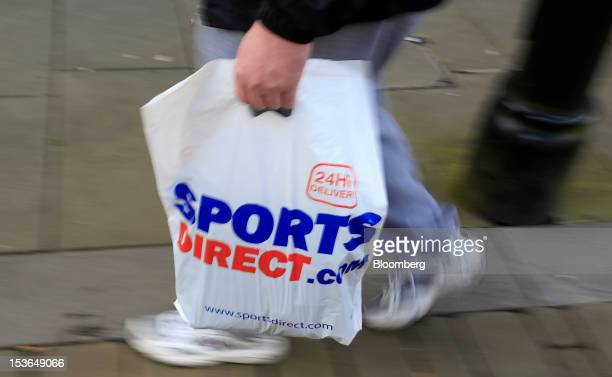 A customer carries a Sports Direct International Plc branded shopping bag in Oldham UK on Saturday Oct 6 2012 JJB Sports Plc a UK sporting goods...